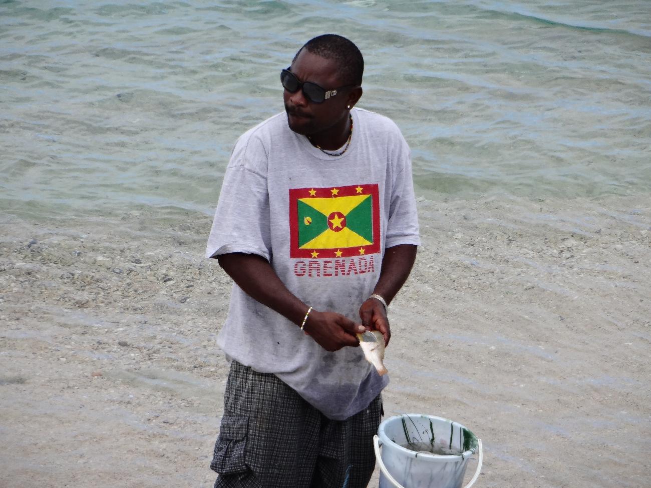 Bartenderen på stranden for å rense fisk til middags gjestene.